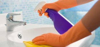 person-in-orange-gloves-cleaning-sink-with-purple-bottle