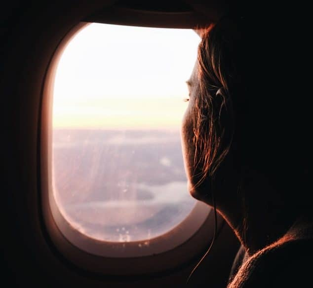 A woman looking out a plane window
