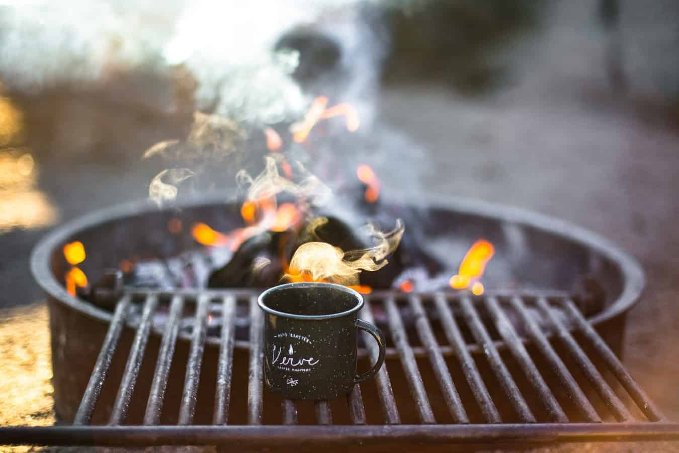 A black mug on a grill in front of a smoking barbecue