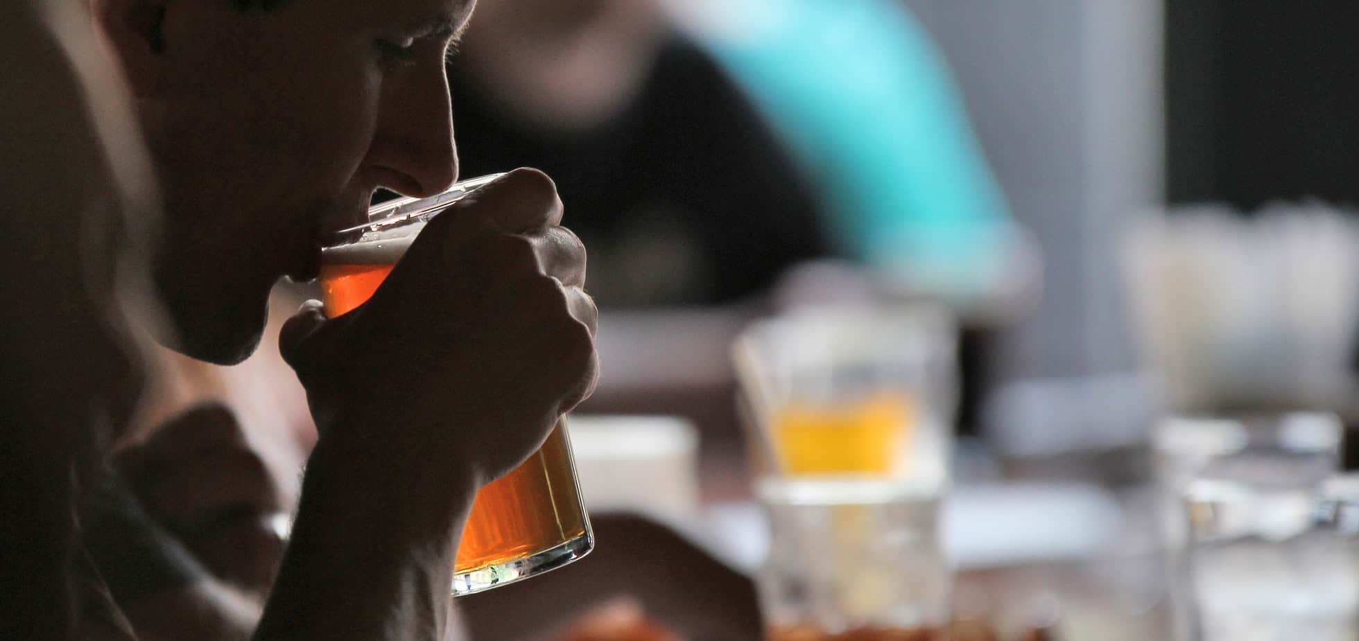 Close up of a boy drinking beer from a pint glass