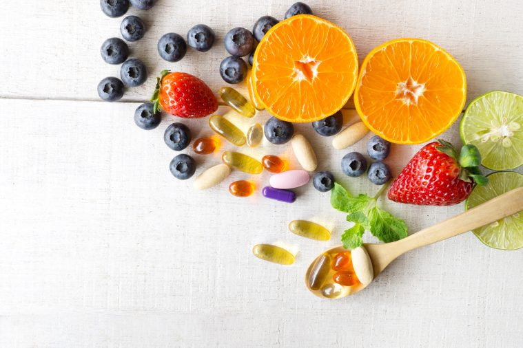 Multivitamins and supplements with fresh and healthy fruits on white wooden background