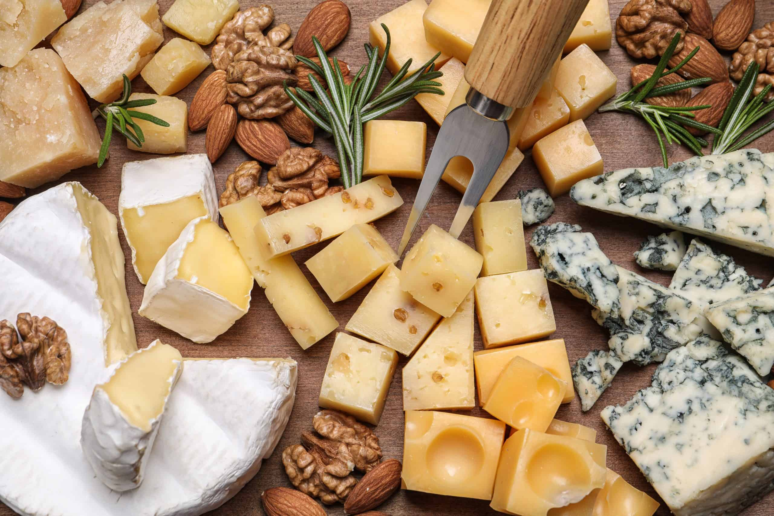 Cheese plate with rosemary and nuts on wooden board, top view